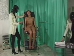 Two dominas are using sex toys on their female slave