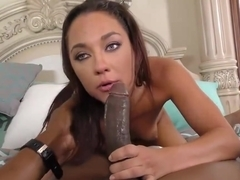 Experienced brunette is gently sucking a big, black cock while kneeling on the floor and loving it