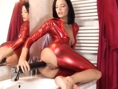 Lusty brunette in red spandex costume is drilling her tight ass hole with a massive sex toy